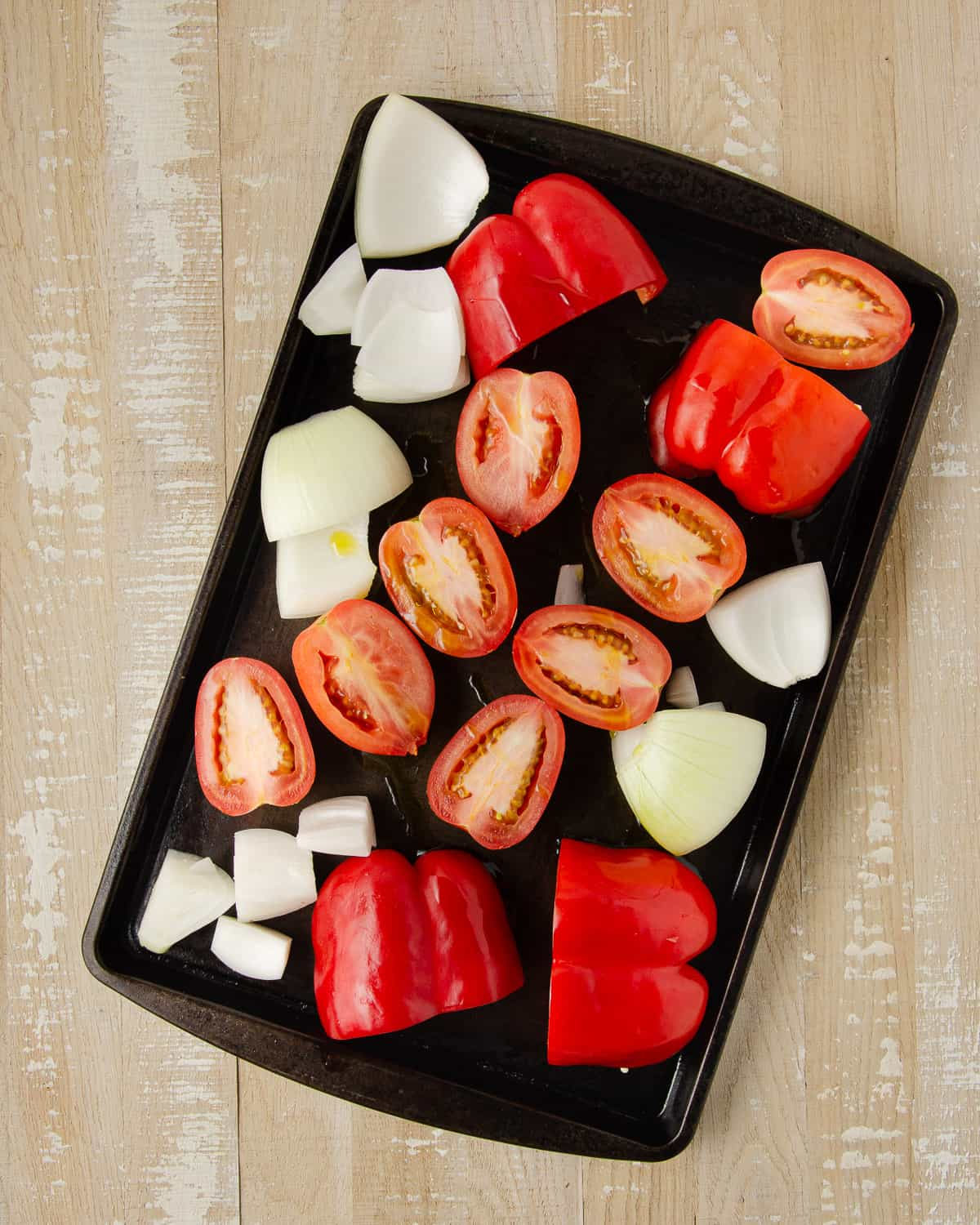 Red bell peppers, onion, and roma tomatoes on a baking sheet before roasting.