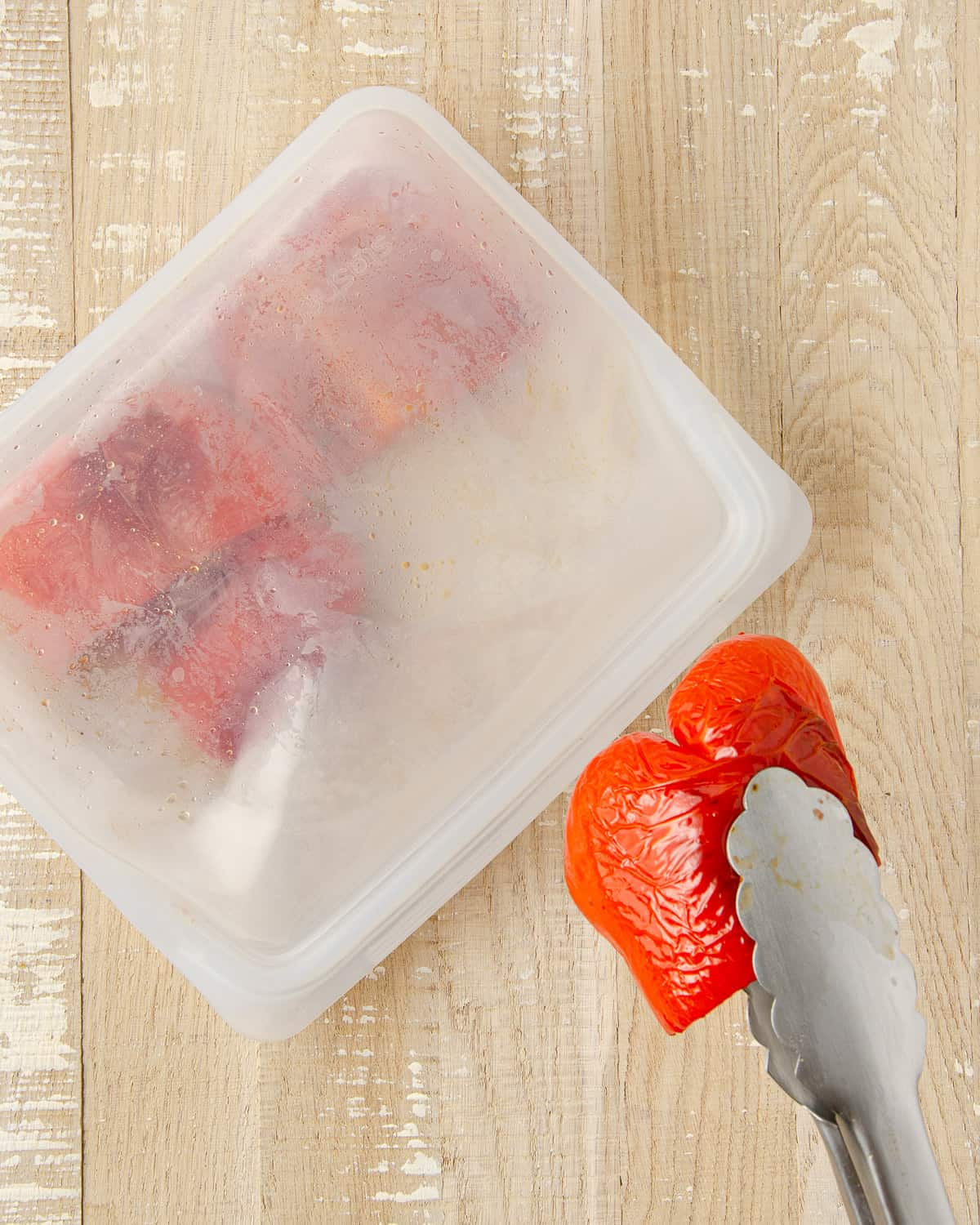 Placing a roasted red pepper in a bag to steam.