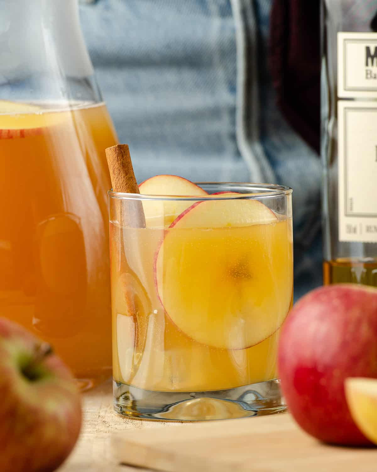 Close up of a spiked apple cider cocktail with a cinnamon stick and apples.