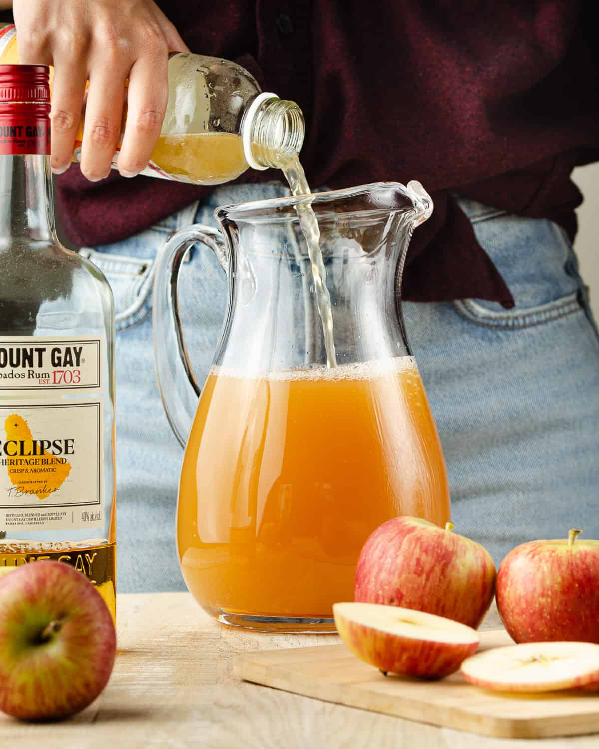 Pouring kombucha into a pitcher of apple cider and rum.