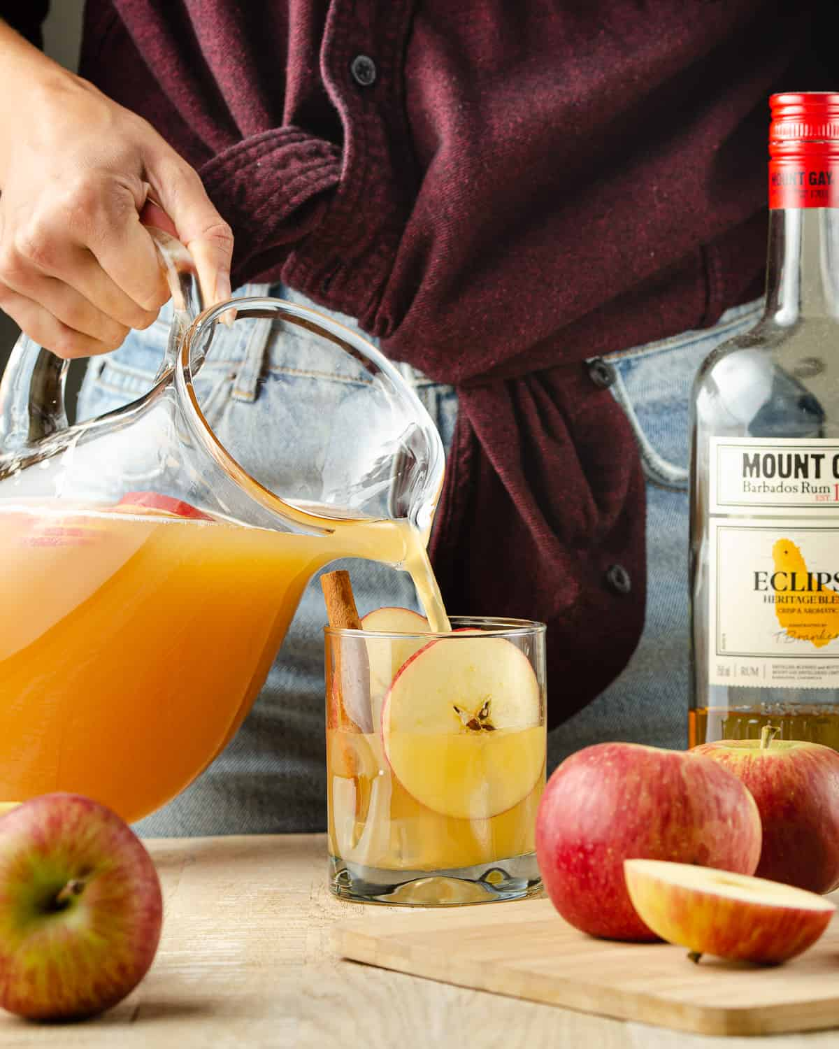 Pouring spiked apple cider into a glass.