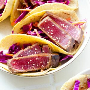 Featured image of a plate of ahi tuna tacos on top of a cabbage slaw.