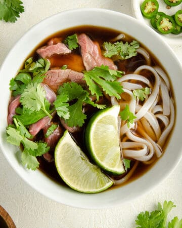 A bowl of gluten free pho with beef topped with two limes and cilantro.