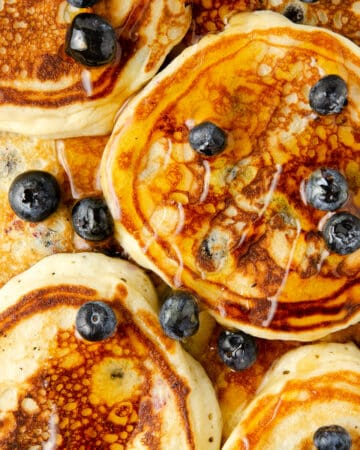 Overhead view of blueberry pancakes topped with fresh blueberries and maple syrup.
