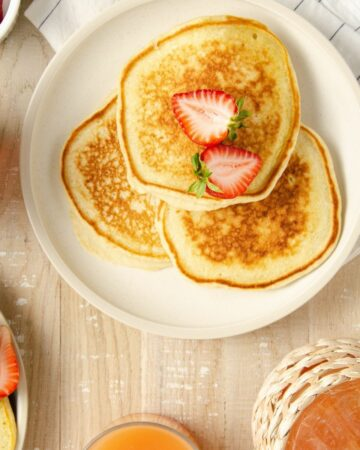 a beige plate of three pancakes topped with halved strawberry with a bowl of strawberries to the bottom, a second plate to the top left, and grapefruit juice