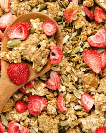 Featured image of protein granola on a brown wooden spoon.