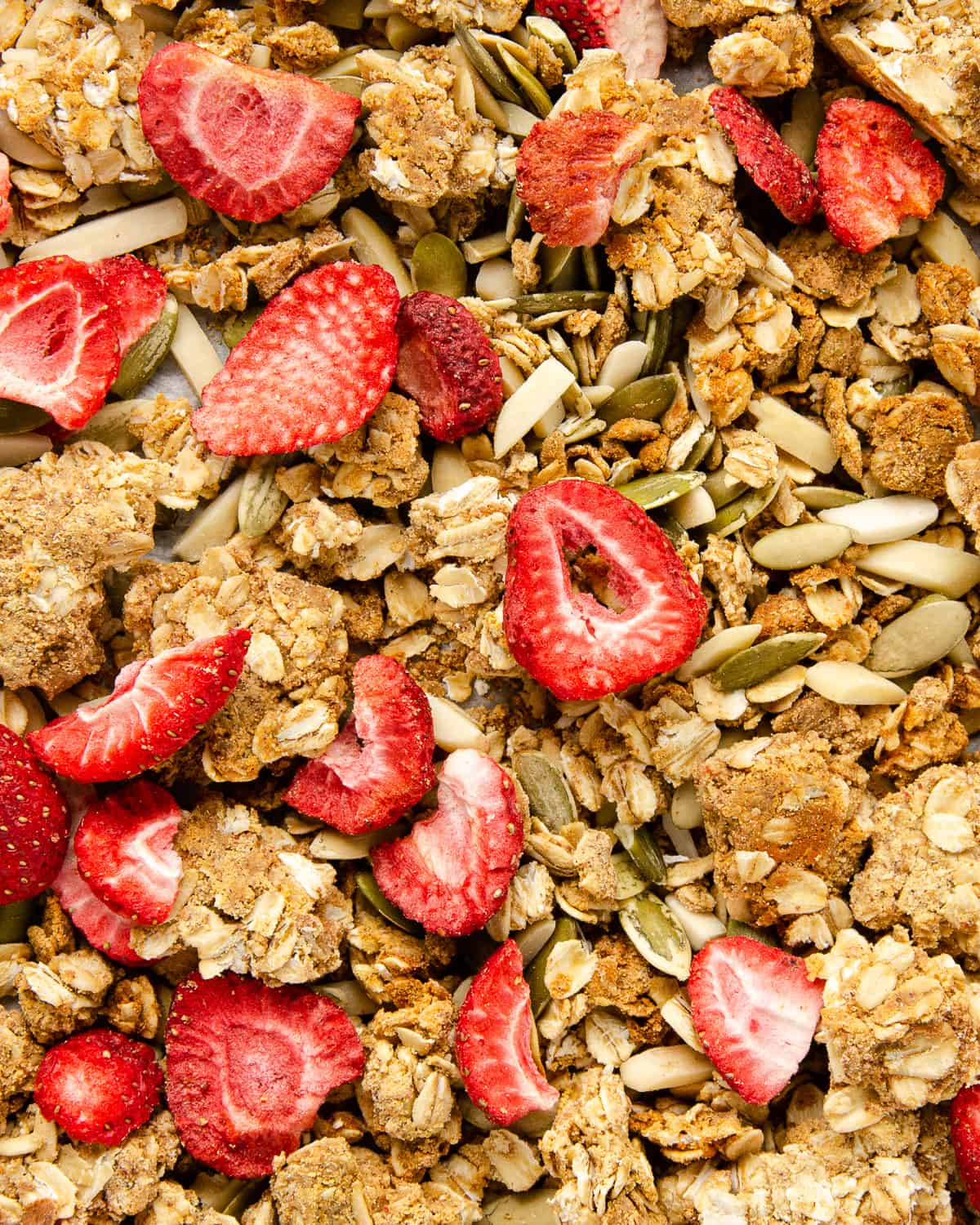 A close up view of granola with mix-in's of seeds, nuts and strawberries.