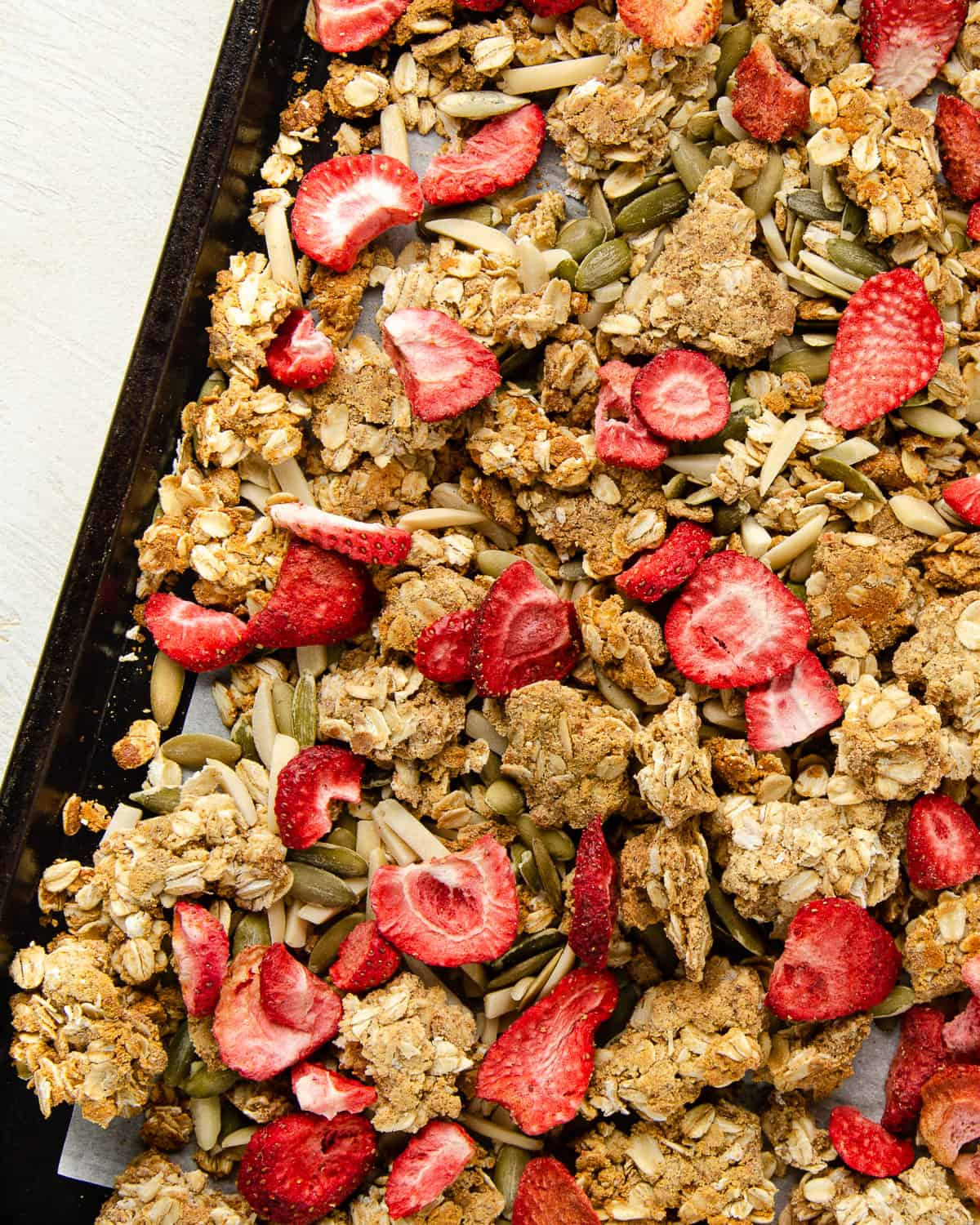 Final view of protein granola crumbles with mix-in's on a baking sheet.