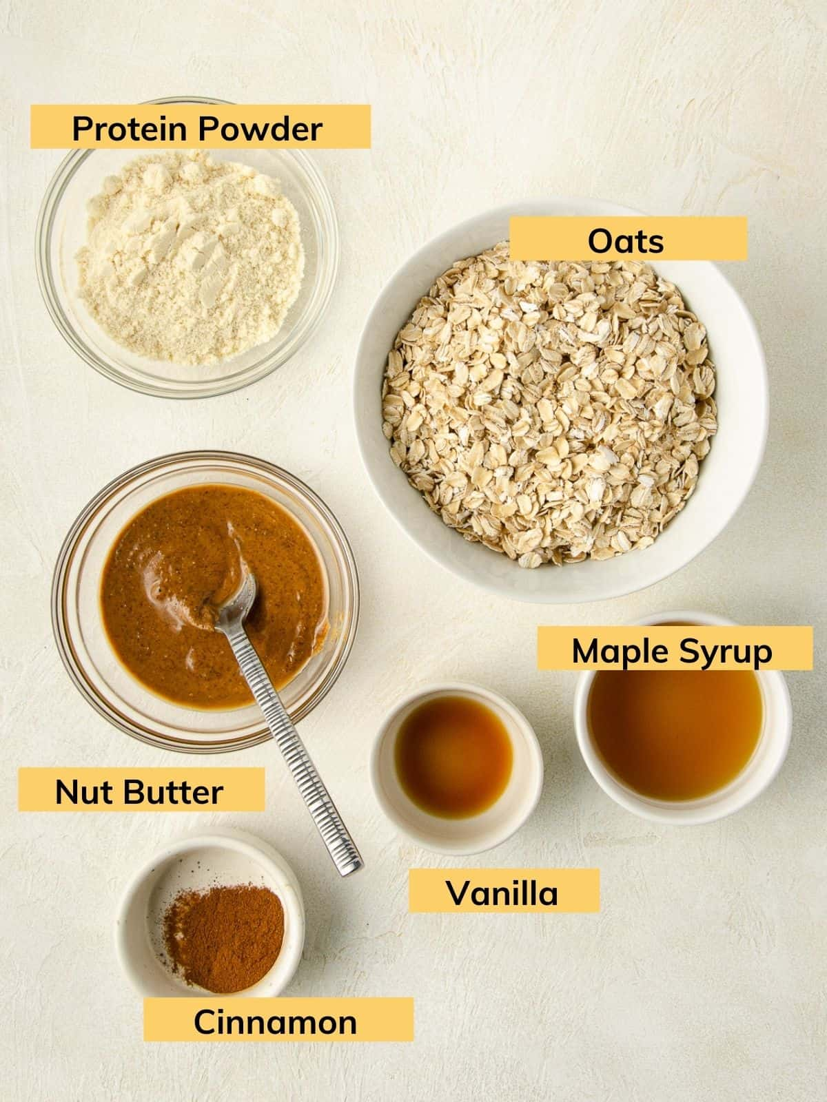 All of the ingredients needed for granola: oats, maple syrup, vanilla, cinnamon, nut butter and protein powder.
