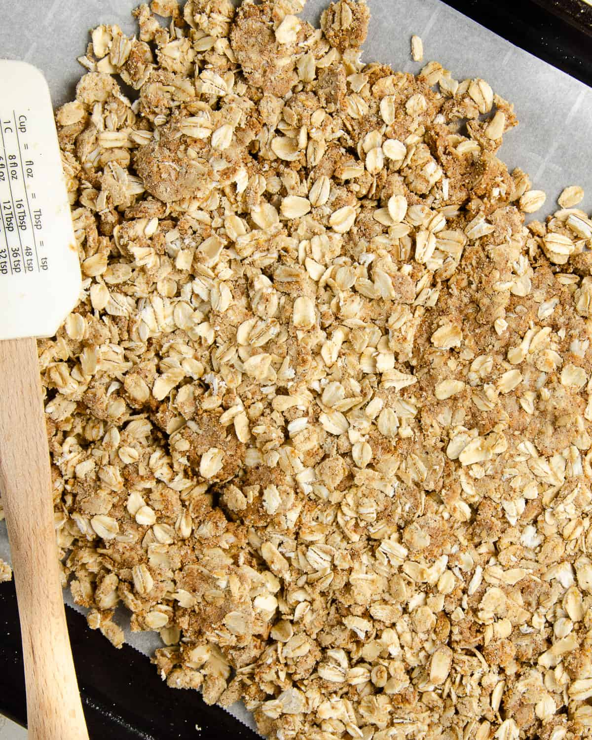 Flattening the protein granola onto parchment lined baking tray before baking.