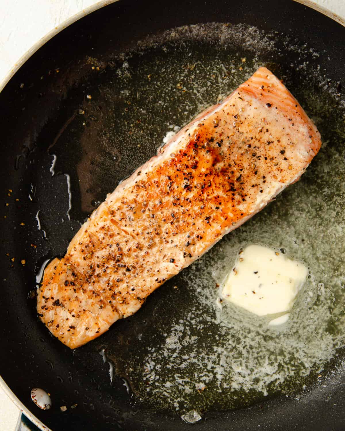 A pan seared salmon filet in the pan with butter.