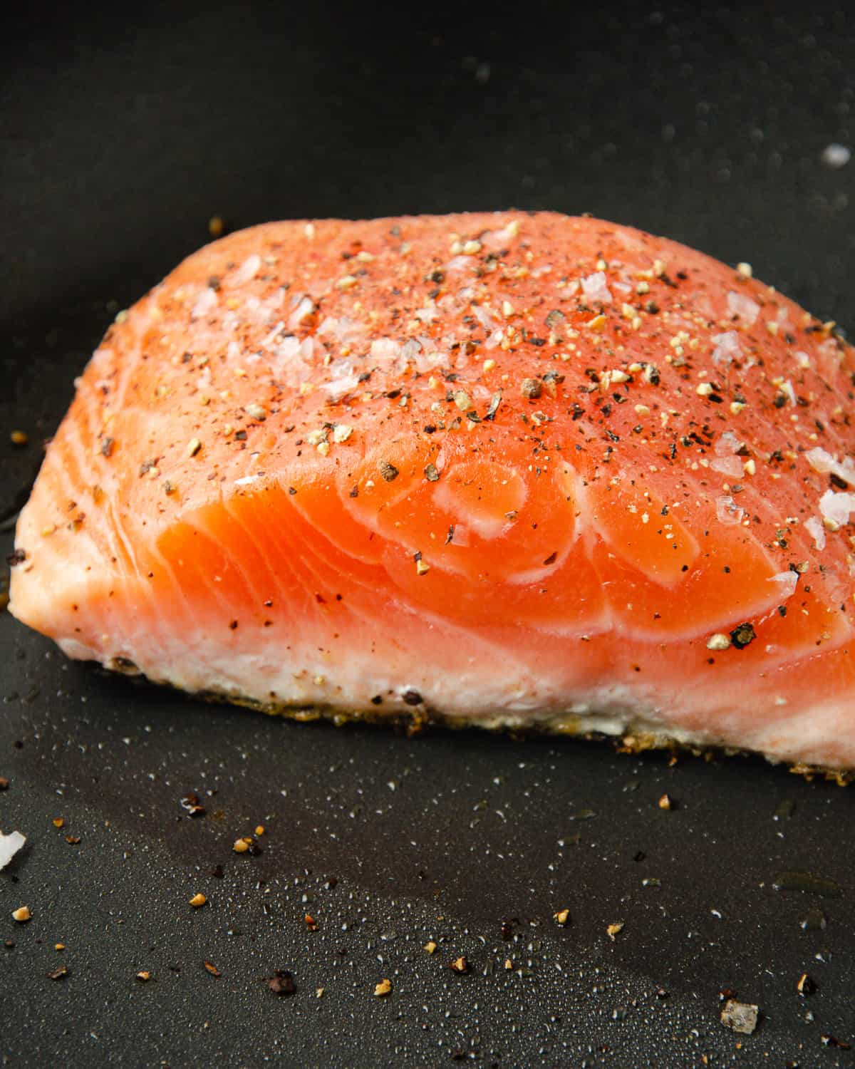 A filet of salmon on the pan that is cooked halfway up.