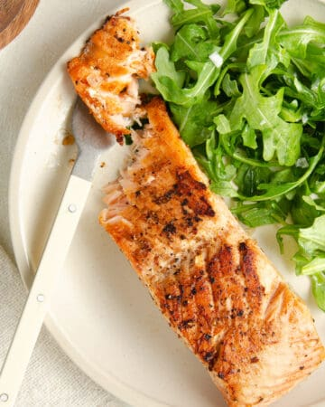 A featured image of a pan seared salmon filet on a plate with a fork piercing a piece of salmon.