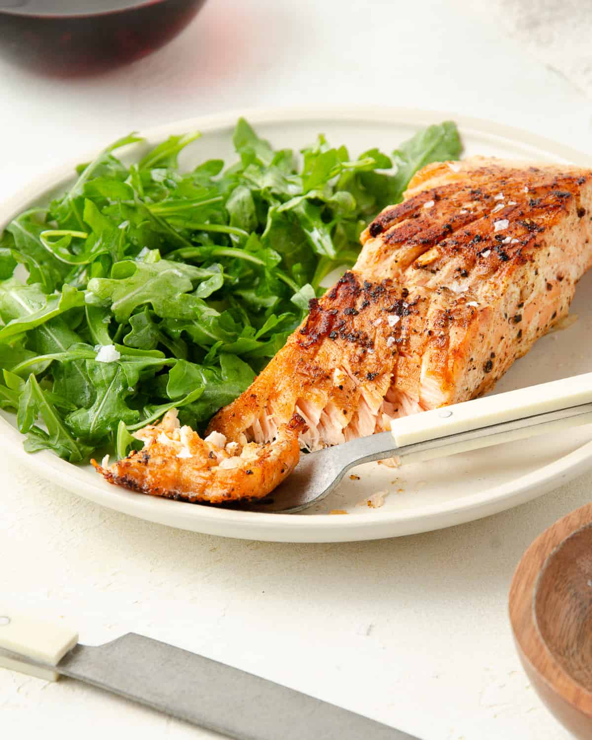 An angle of a salmon filet on a plate with a fork piercing the filet.