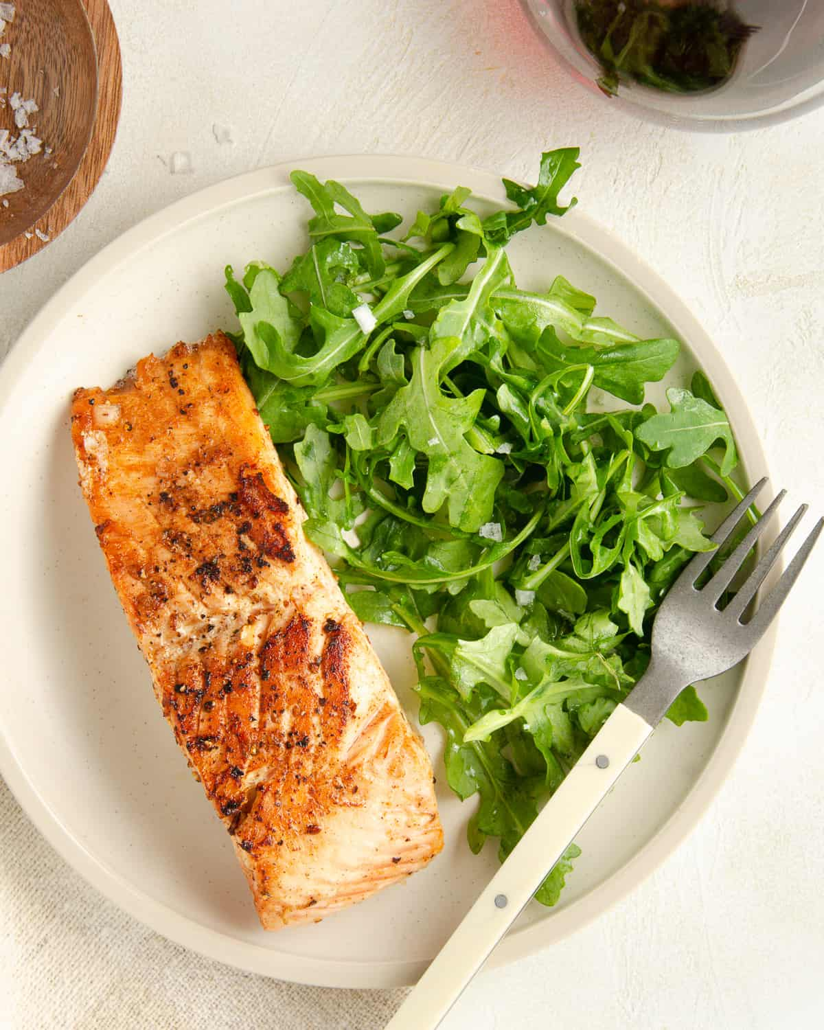A plate of arugula with a filet of salmon.