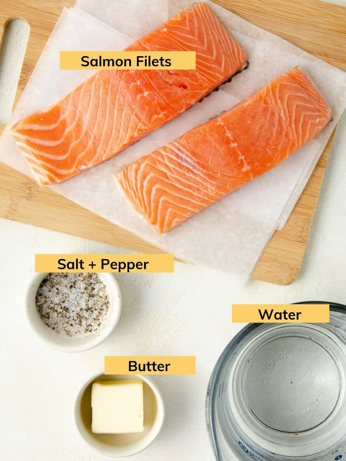 Two filets of salmon on a cutting board next to water, salt, pepper and butter.