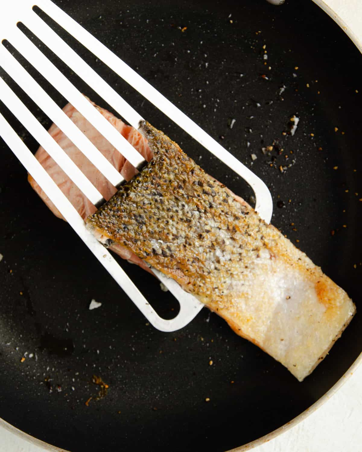 Removing the skin off the salmon filet by sliding the spatula between the skin and filet.