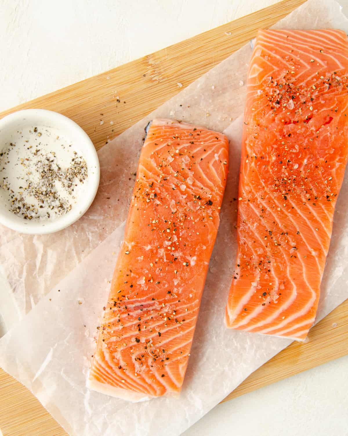 Two filets of salmon that are seasoned heavily with salt and pepper.