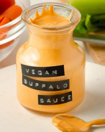 Angled view of a jar of vegan buffalo sauce with some sauce on a spoon.