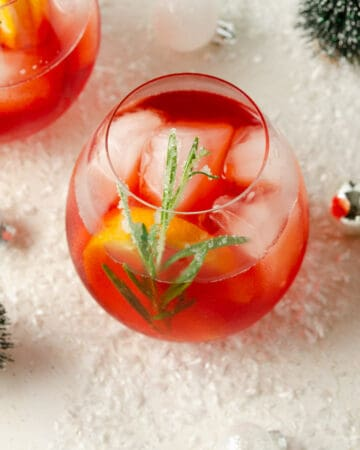 Featured image of a Winter Aperol Spritz in a glass with rosemary and orange garnish.